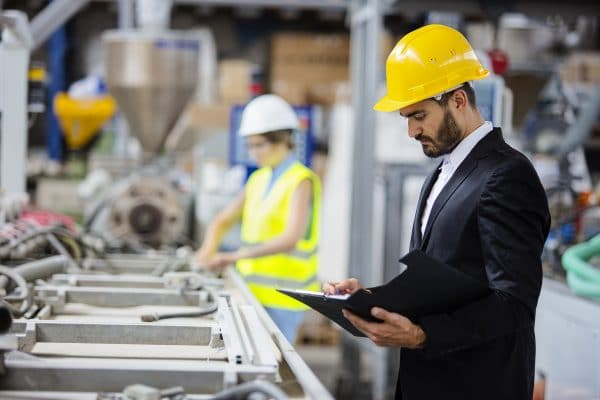 Man in a suit and yellow hard hat looking at parts in a factory and taking notes