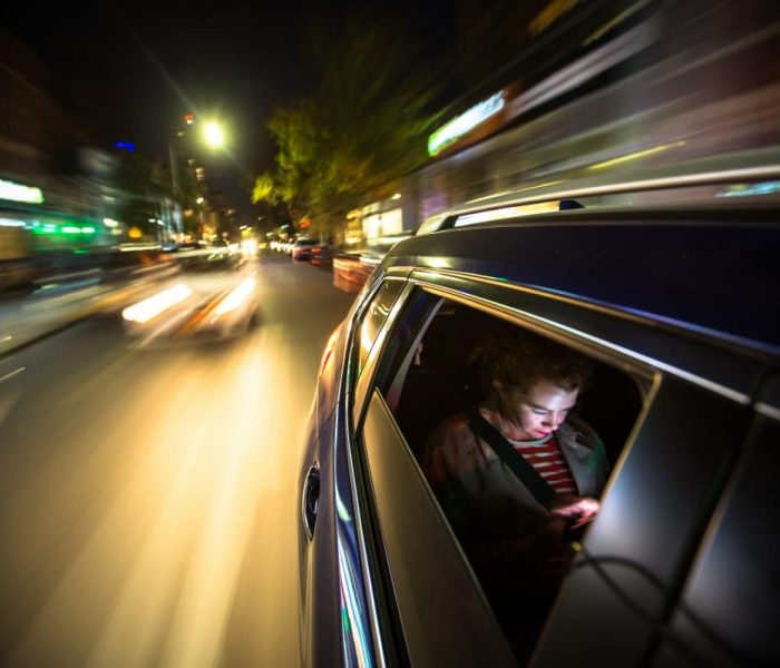 A woman sits in the back of a car, possibly a rideshare, looking at her mobile phone. The lights of New York City streak past.