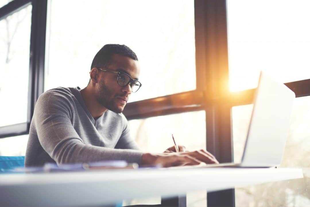 Man looking at computer screen while taking notes.
