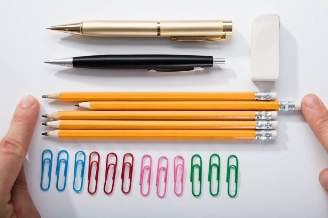 Lined up pens, pencils and paper clips. One of the pencils is out of line. A person is pushing it in line.