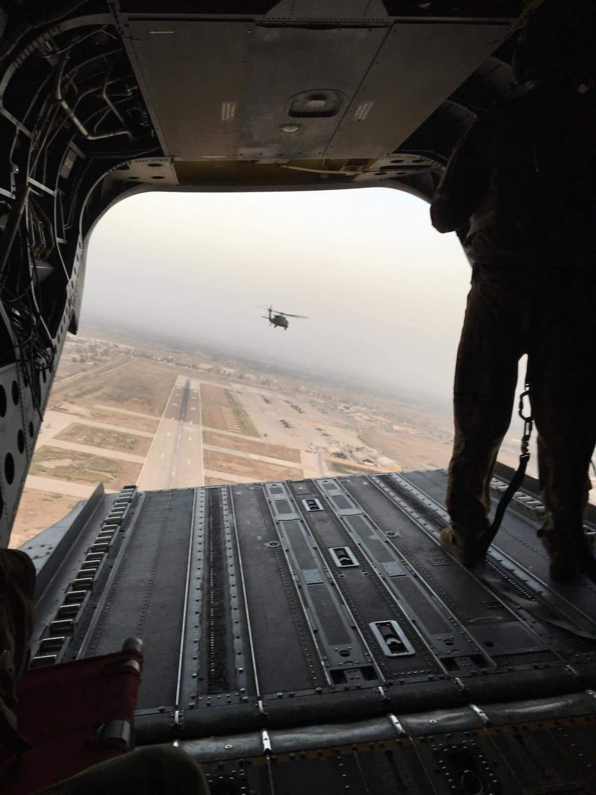 Man standing in the open back of a helicopter, looking to another helicopter.