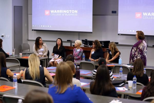 Six women at the front of a classroom speaking to a room of female students