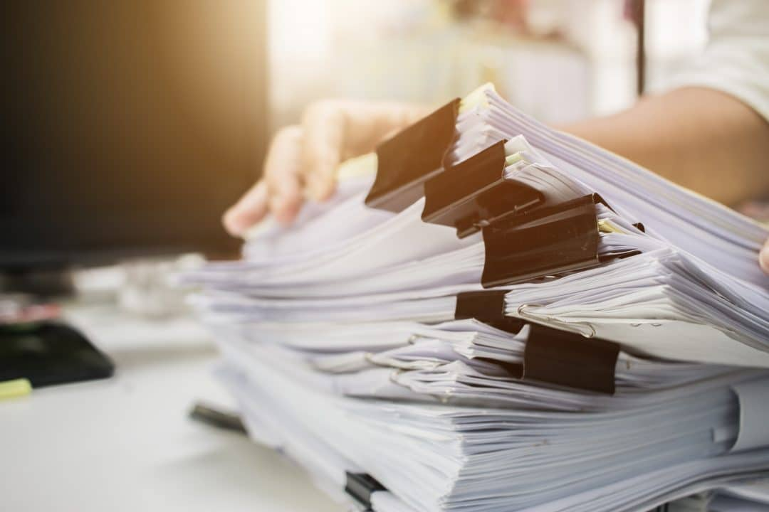 Businessman hands searching information in Stacks of paper files on work desk office, business report papers or piles of unfinished documents achieves with clips on offices indoor, Business concept