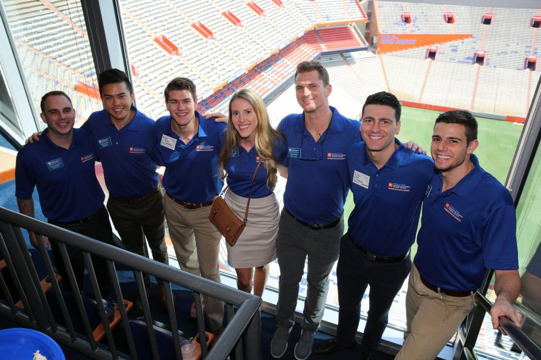 Seven real estate students pose for a photo in Ben Hill Griffin Stadium