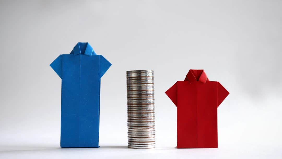 Blue and red shirts made of paper with piles of coins in between. The concept of gender employment and wage gap in the enterprise.