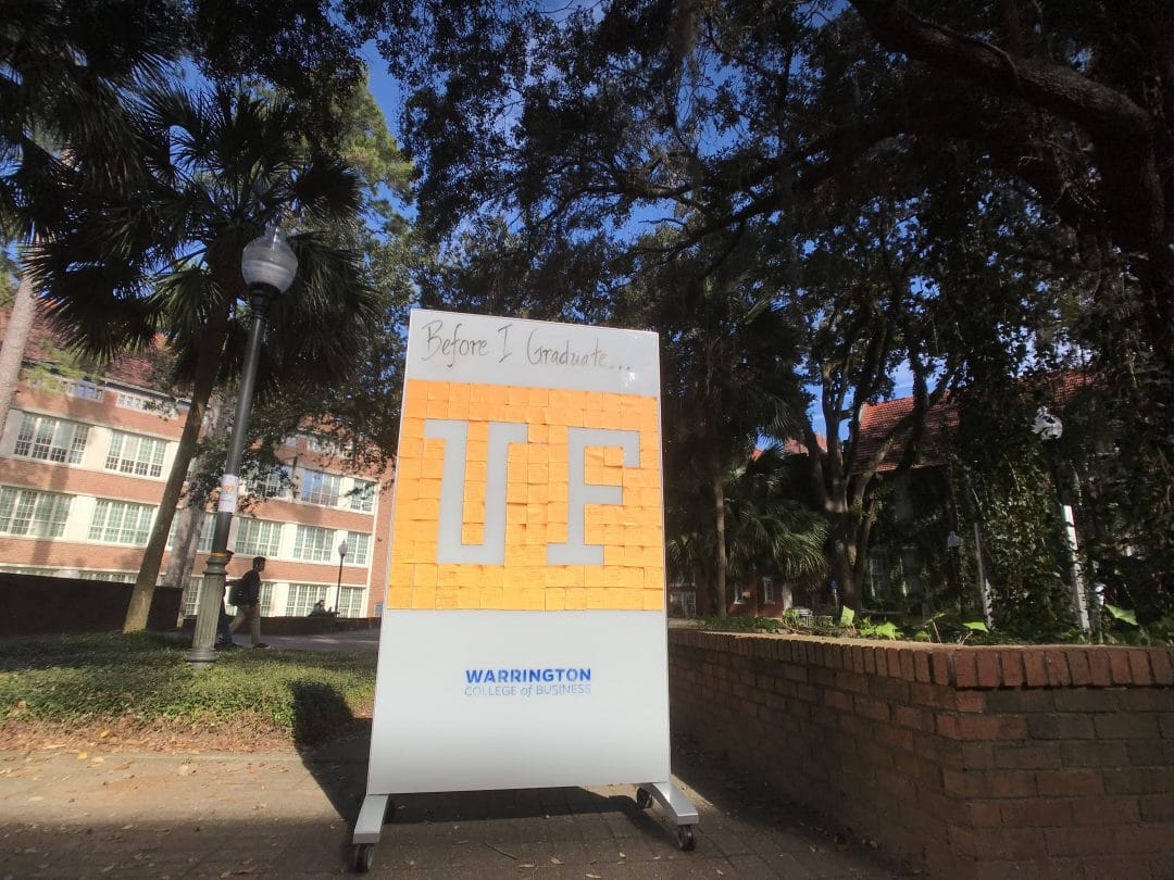 A large white board on wheels sits in a green courtyard. The white board reads Before I graduate with the UF logo, which is made of post it notes