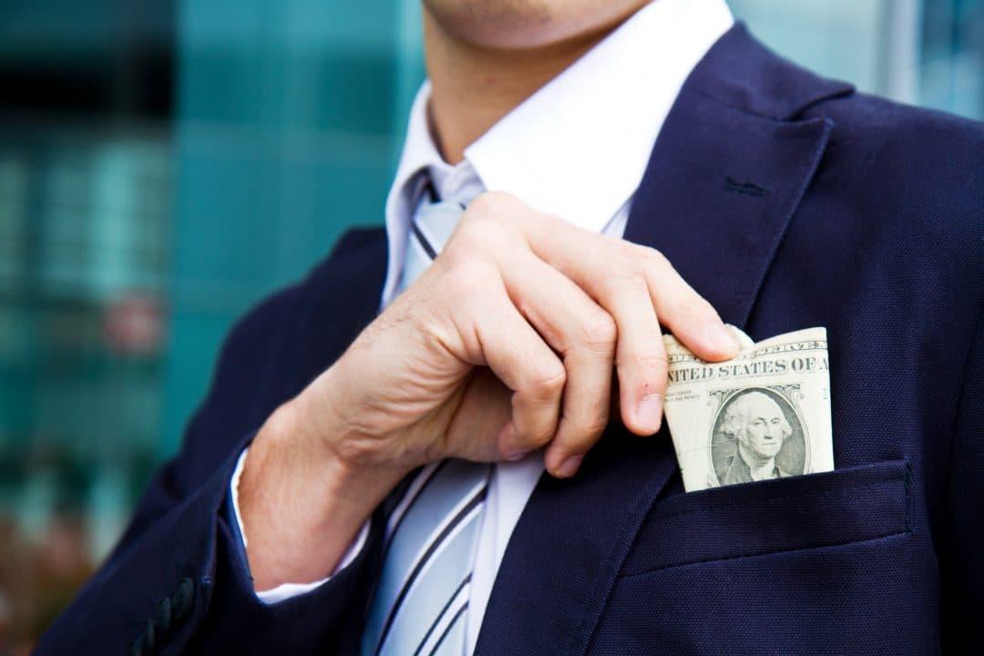 Business man putting money in pocket