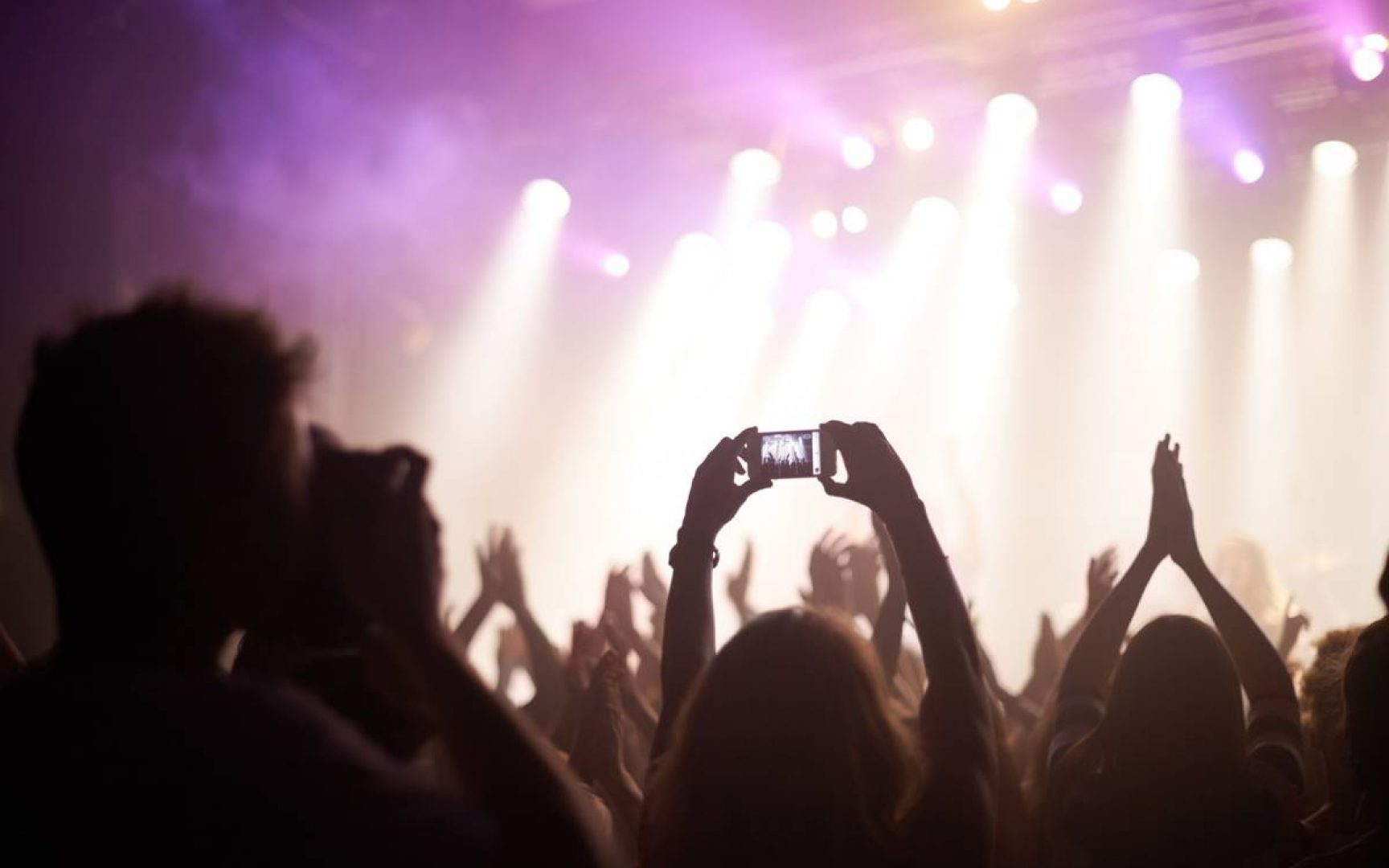 Person standing in a crowd at a concert taking a photo of the stage.
