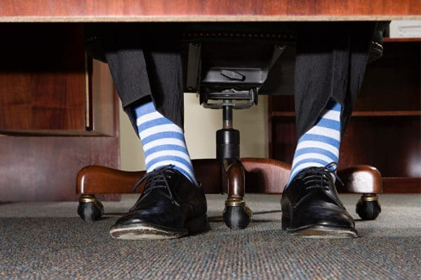 View of businessman with striped socks from under a desk.