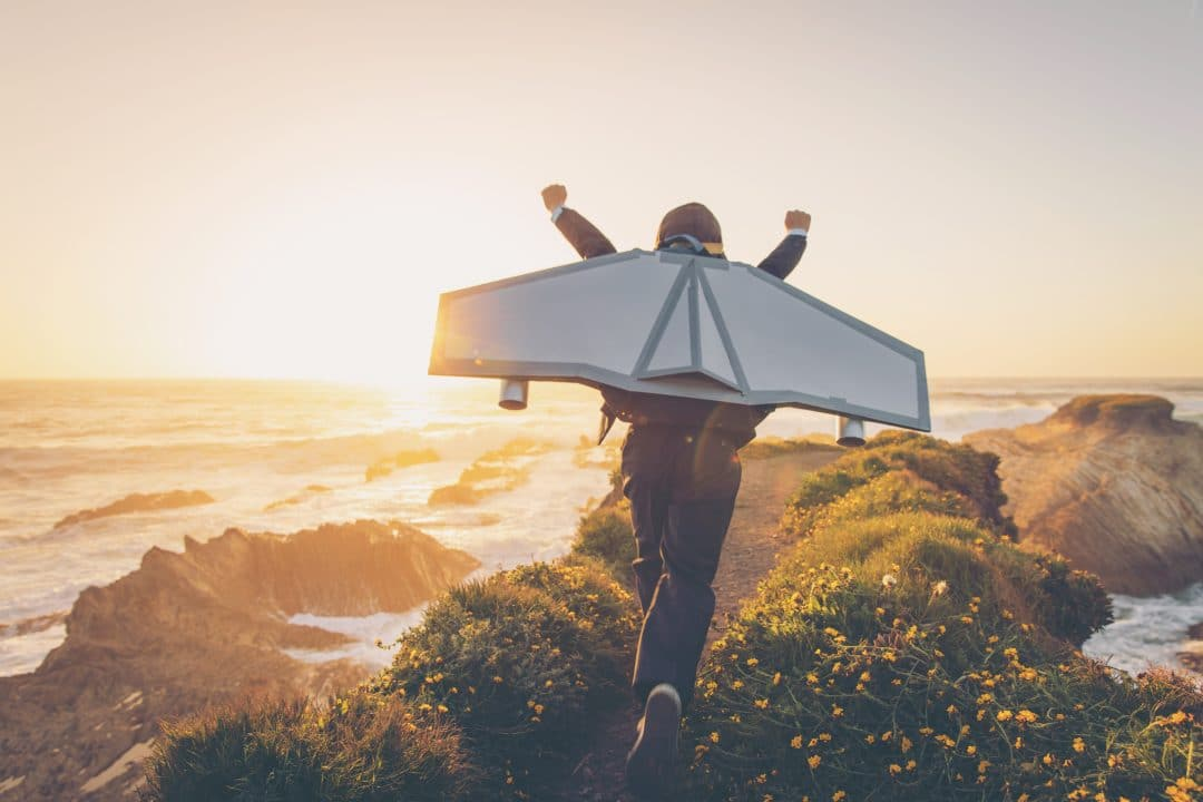 A young man dressed in business suit and tie wears a homemade jetpack and flying goggles raises his arms in the afternoon sun while running to take off into the air on an outcropping above the surf in Montana de Oro State Park, California. This young entrepreneur is ready to take his new business to new heights.