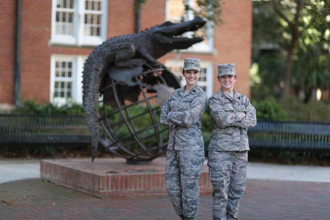 Jasmin Snodgress and Kathryn Eifert stand in front of the Gator Ubiquity Statue