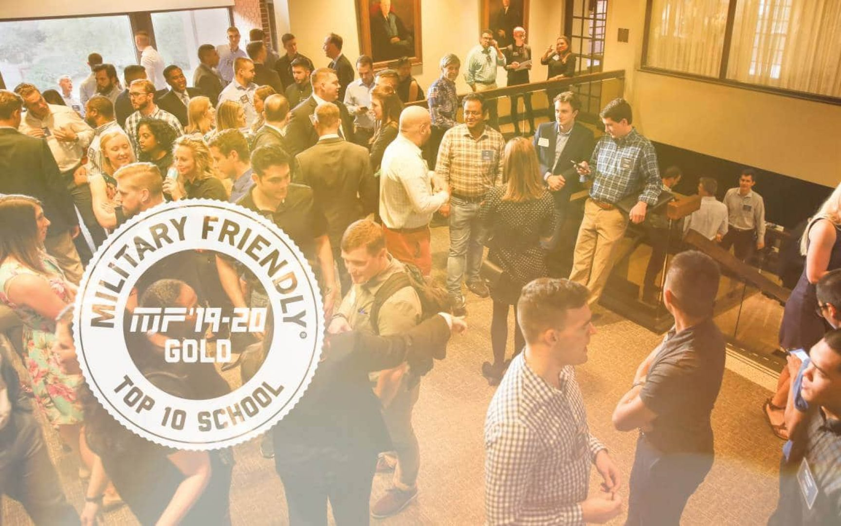 UF MBA students network prior to an event with former Chairman of the Joint Chiefs of Staff General Martin E. Dempsey, U.S. Army, Retired. The military friendly top 10 ranking logo is in the corner of the photo of the students.