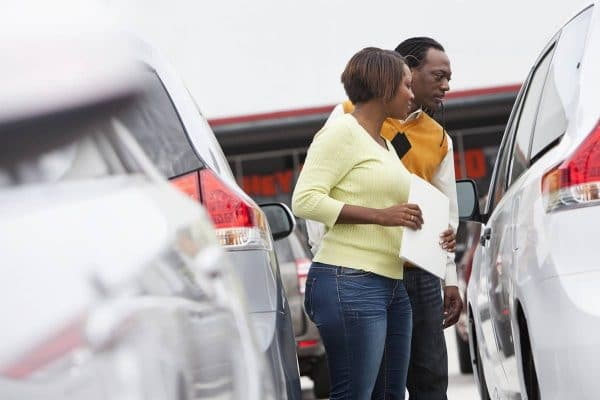 Man and woman looking at multiple cars trying to make a decision about which to choose.
