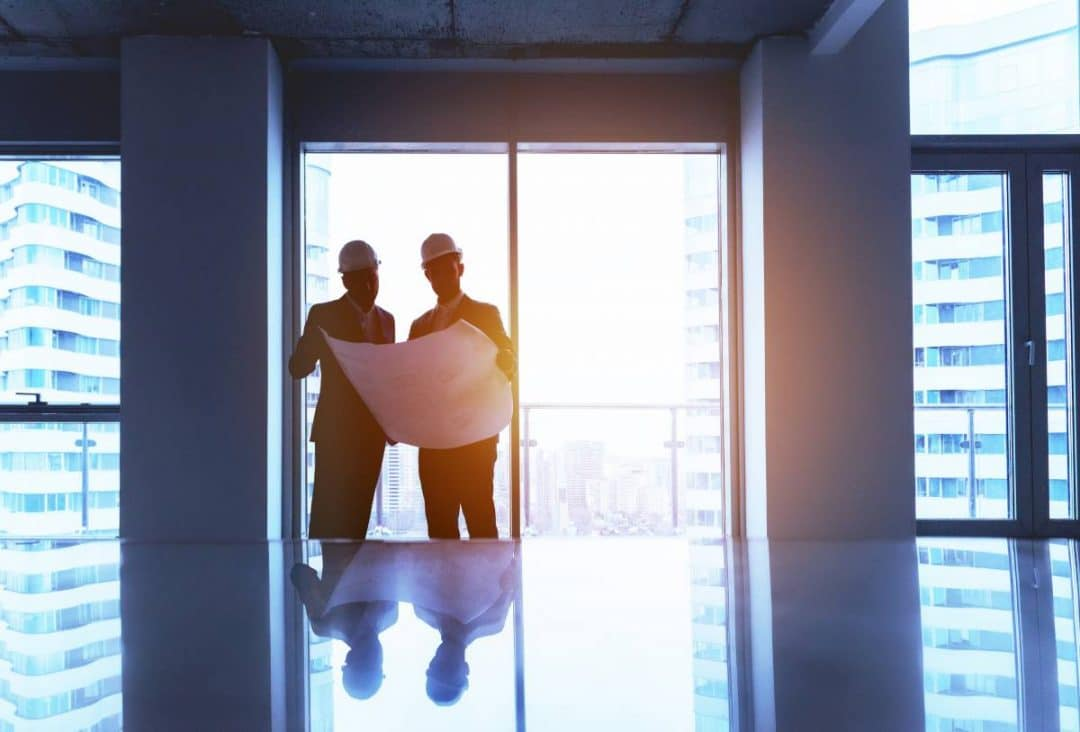 Engineer and businessman discussing project with big plan in empty office against window