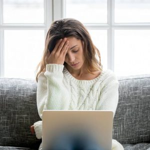 Young woman sitting on a couch looking at a computer. She holds her hand up to her forehead looking stressed.