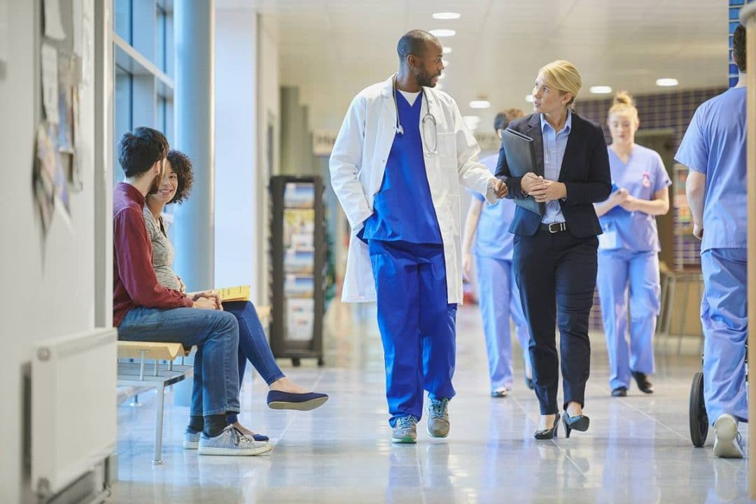 A doctor and hospital administrator walk down a body hospital hallway with nurses and patients in the background.