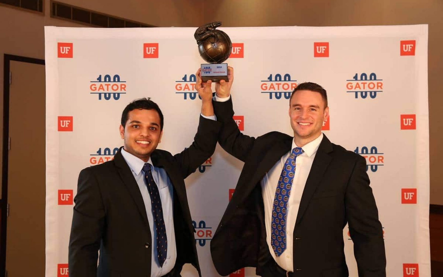Karthik Shanadi and Luke McGurrin hold up their Gator100 trophy