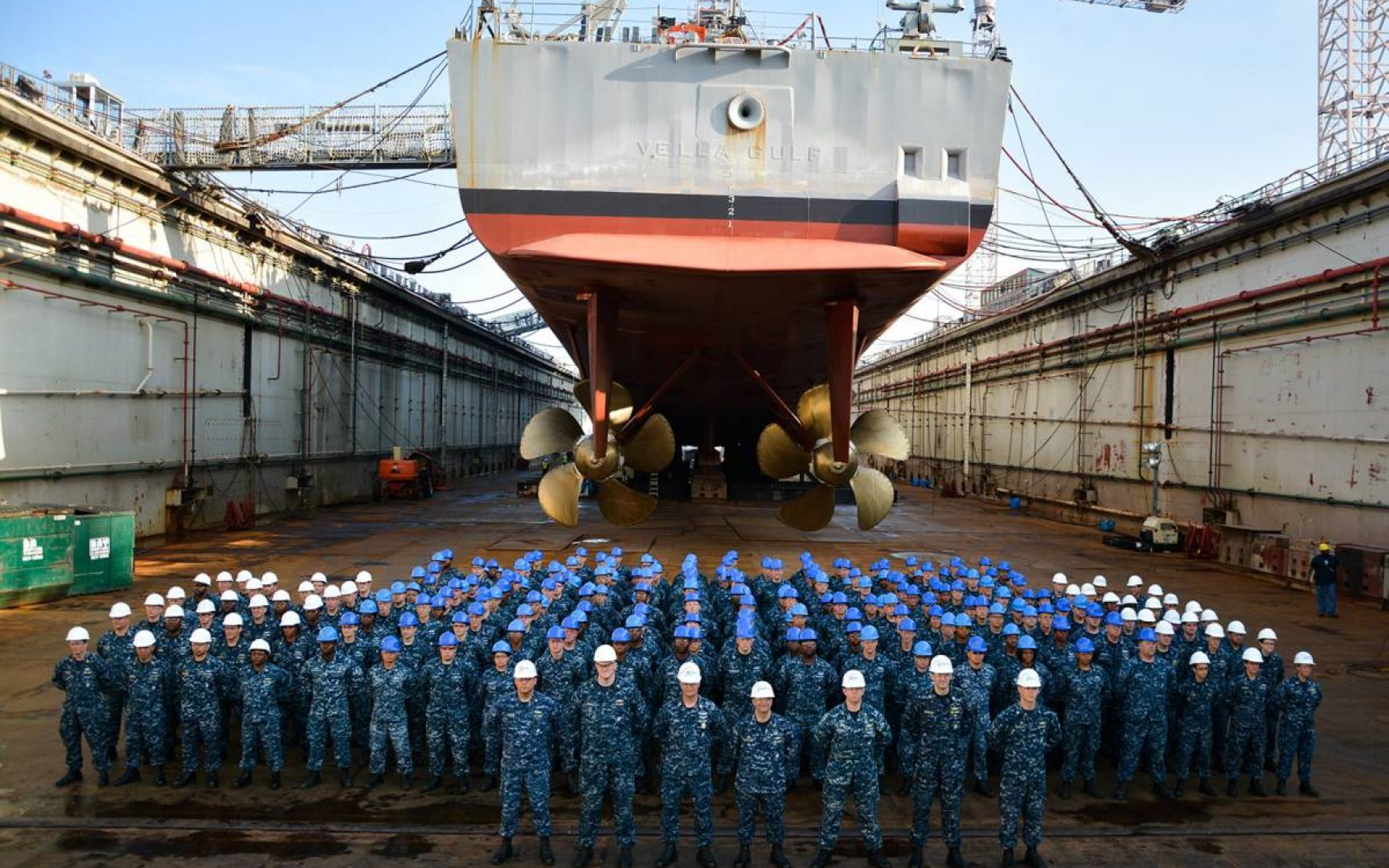 Large group of uniformed soldiers stand in formation in front of a large ship