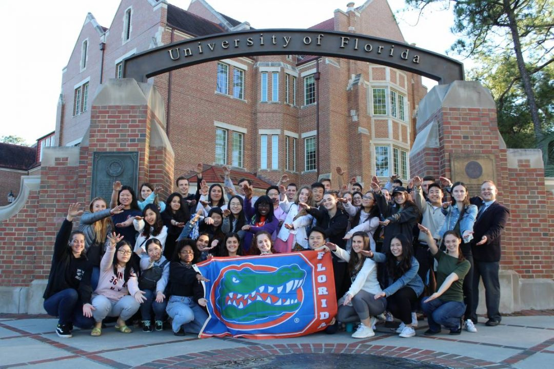 Group of students doing the Gator Chomp while holding a UF flag in front of Heavener Hall
