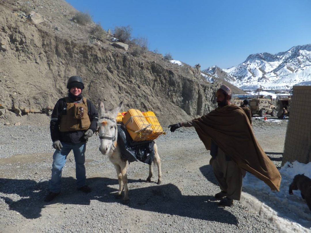 Javier Castano with a donkey packed with supplies next to a local man