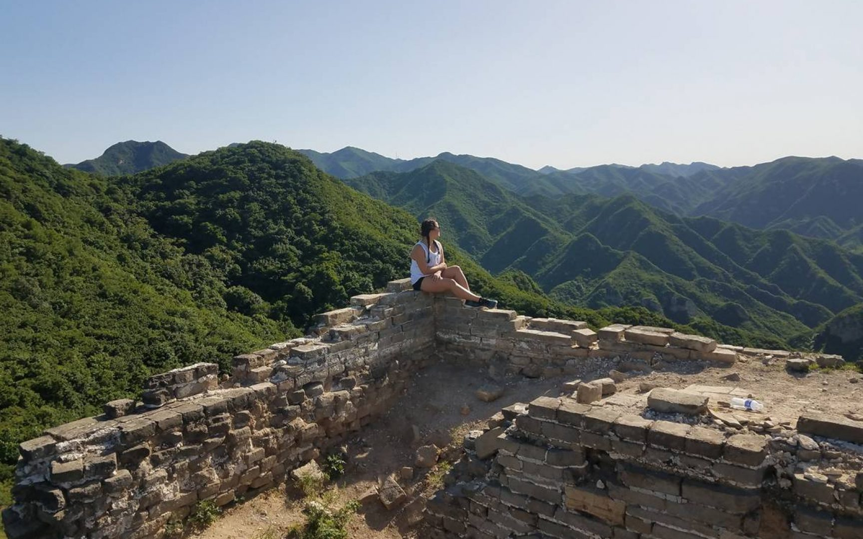 A female student sits on the Great Wall of China