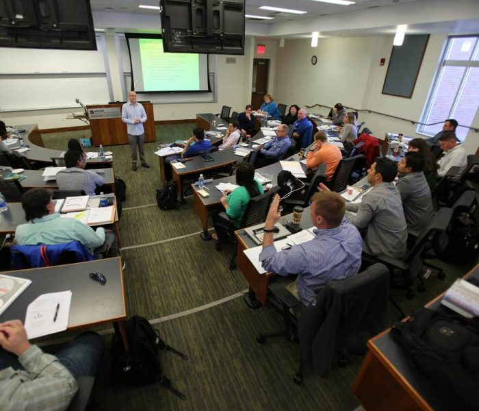 Executive MBA students in a classroom listening to Professor Amir Erez