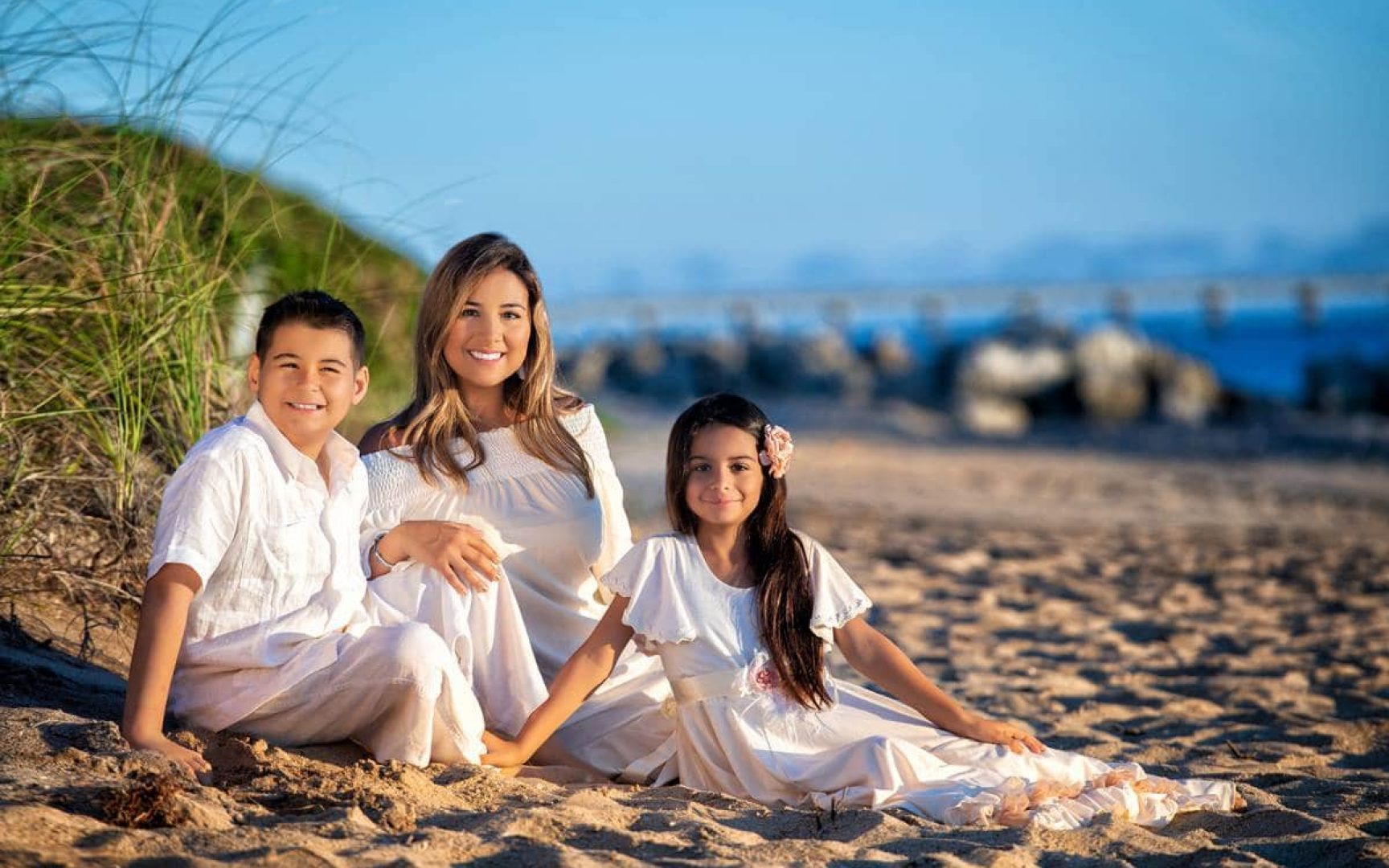 Erika with her Tommy and Gabriela posing for a family photo on the beach.
