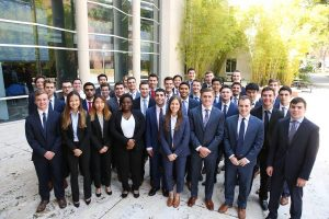 Large group of students in business suits pose for a photo