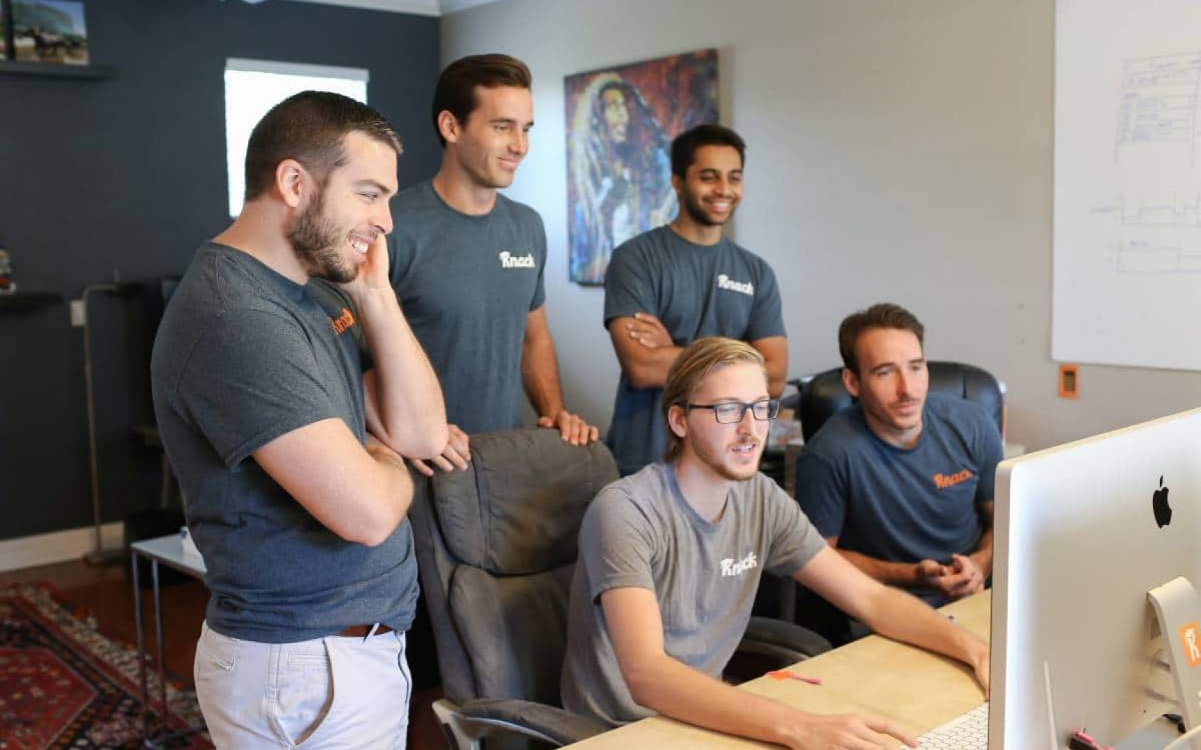 Knack team members look at a computer in their office space.