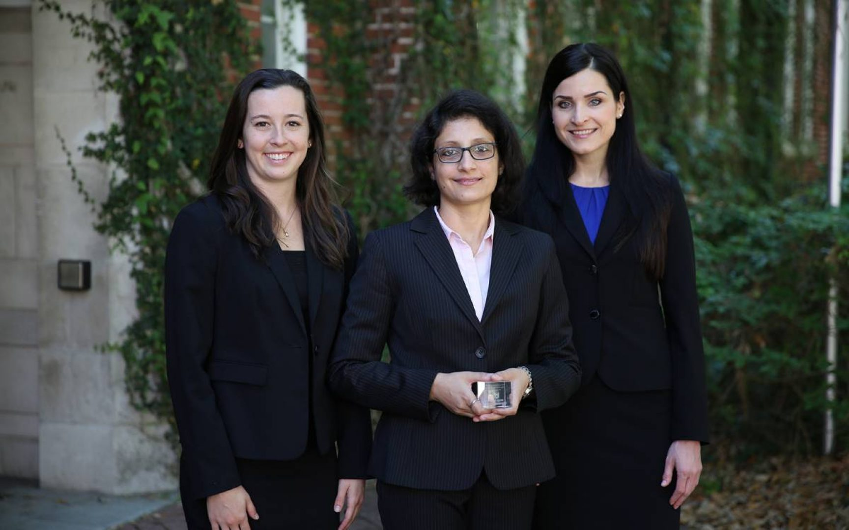 Three female students in suits pose for a photo with their trophy