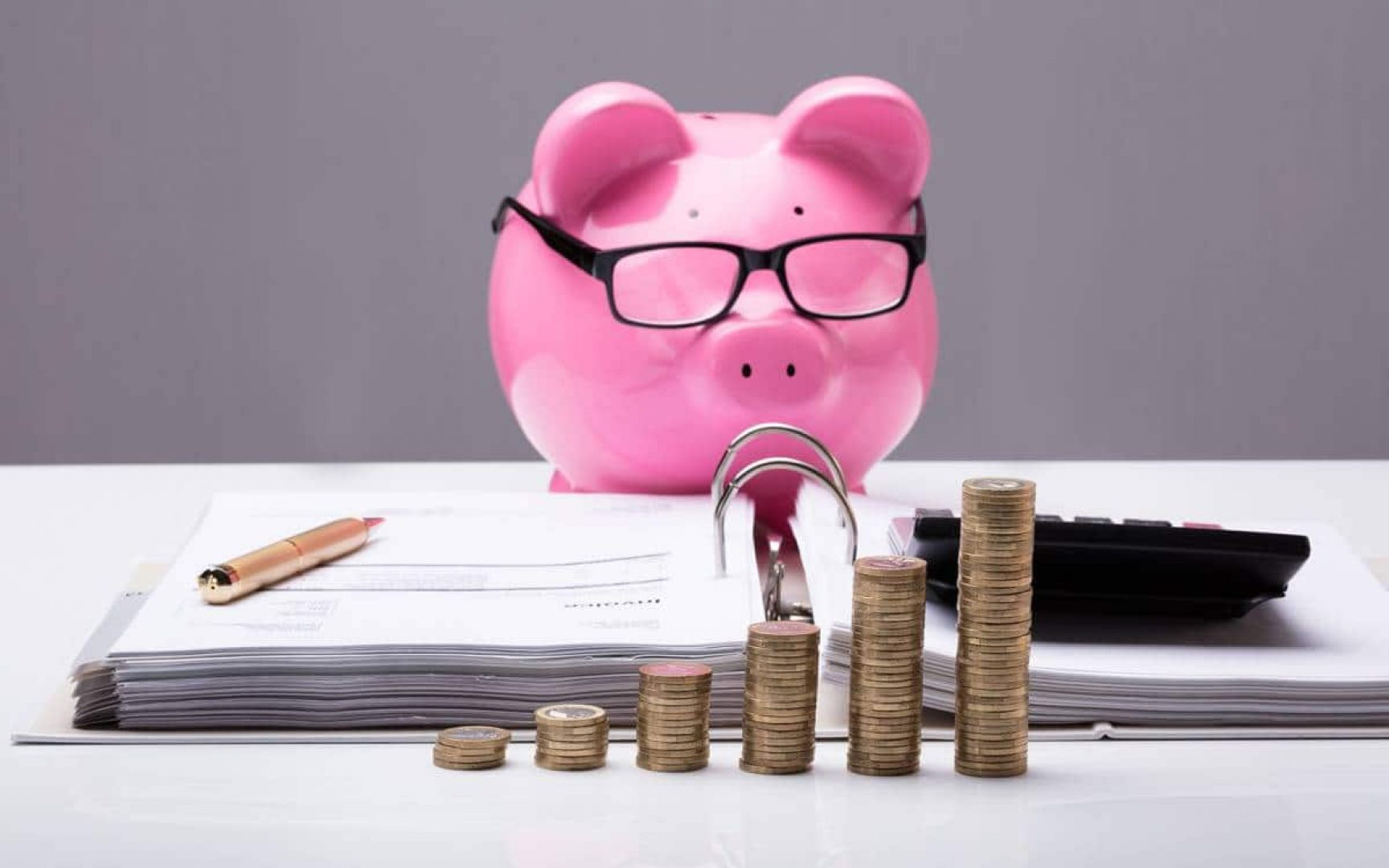 Piggy bank wearing glasses looking at paper and a calculator with stacks of coins in front