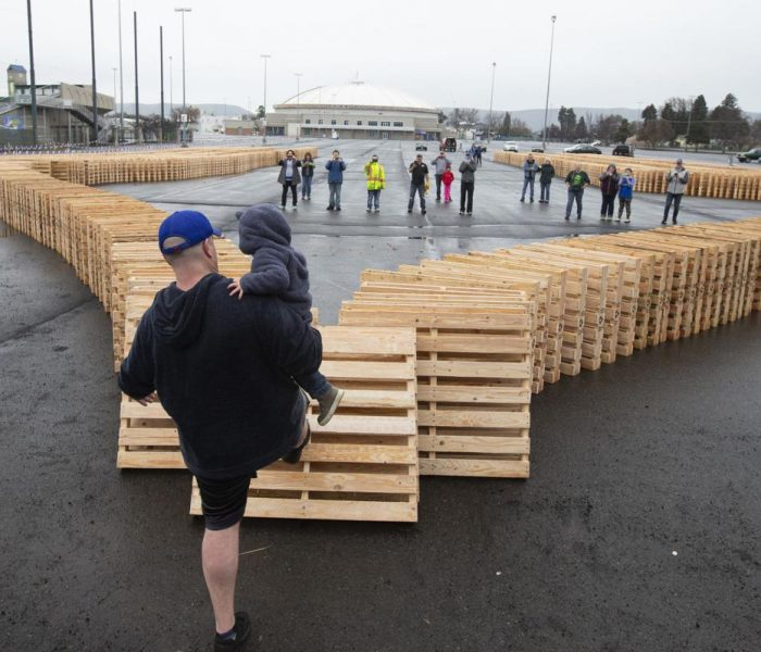 Joe Ketterer and his son Hunter Ketterer kick down the first pallet in a chain of 1,500.