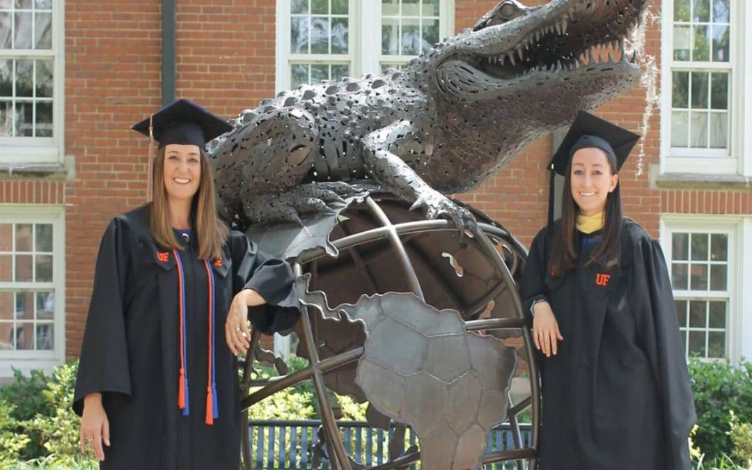 Angel and Morgan Pinkerton stand next to the Gator Ubiquity Statue in their graduation caps and gowns.