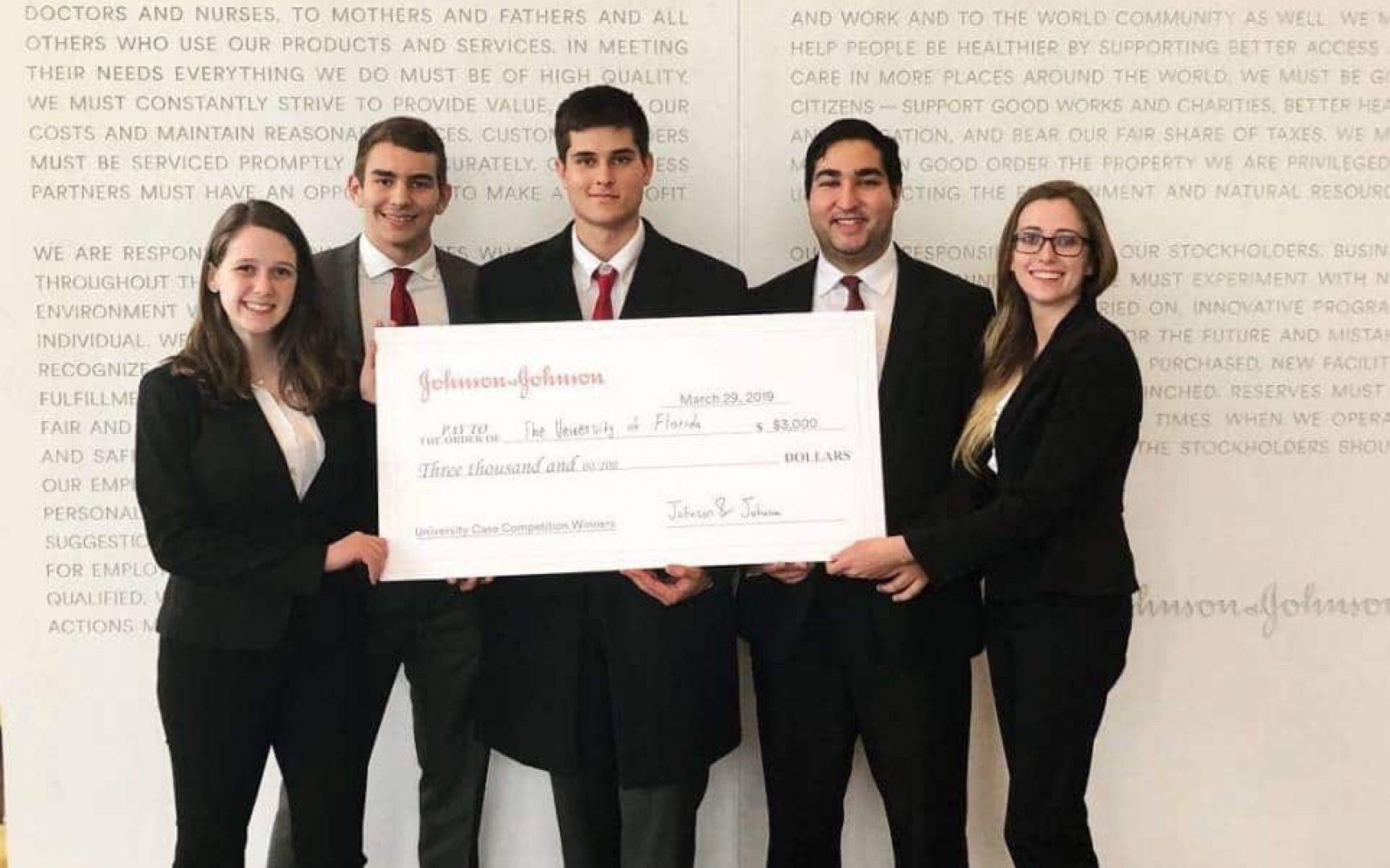 The winning team of Heavener School of Business students with their check from the Johnson & Johnson Case Competition.