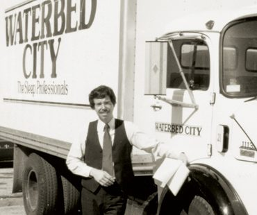 Keith Koenig stands in front of a Waterbed City delivery truck.