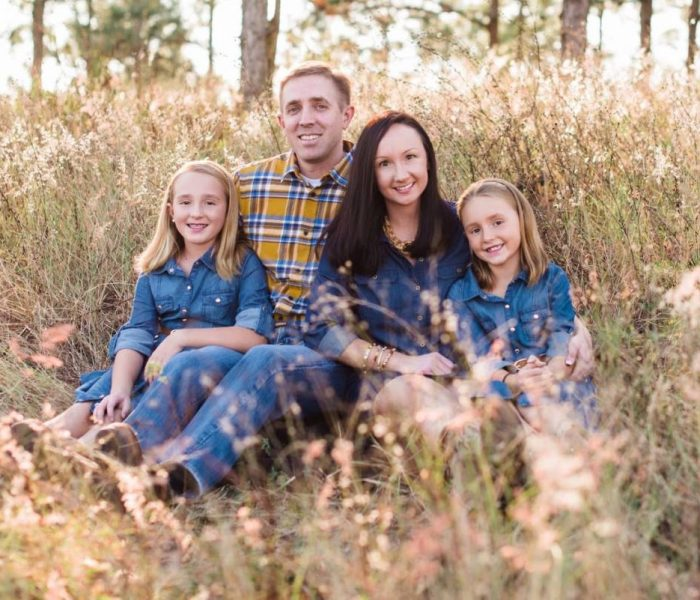 Daniel Hunt and his wife and two daughter sit in a field for a family photo.