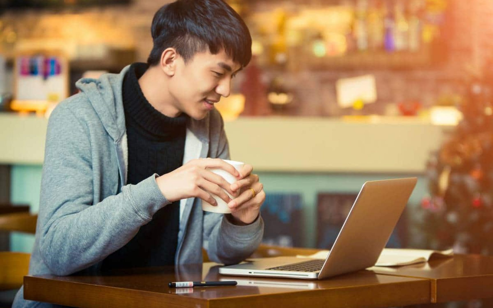 Young man looking at a computer drinking coffee