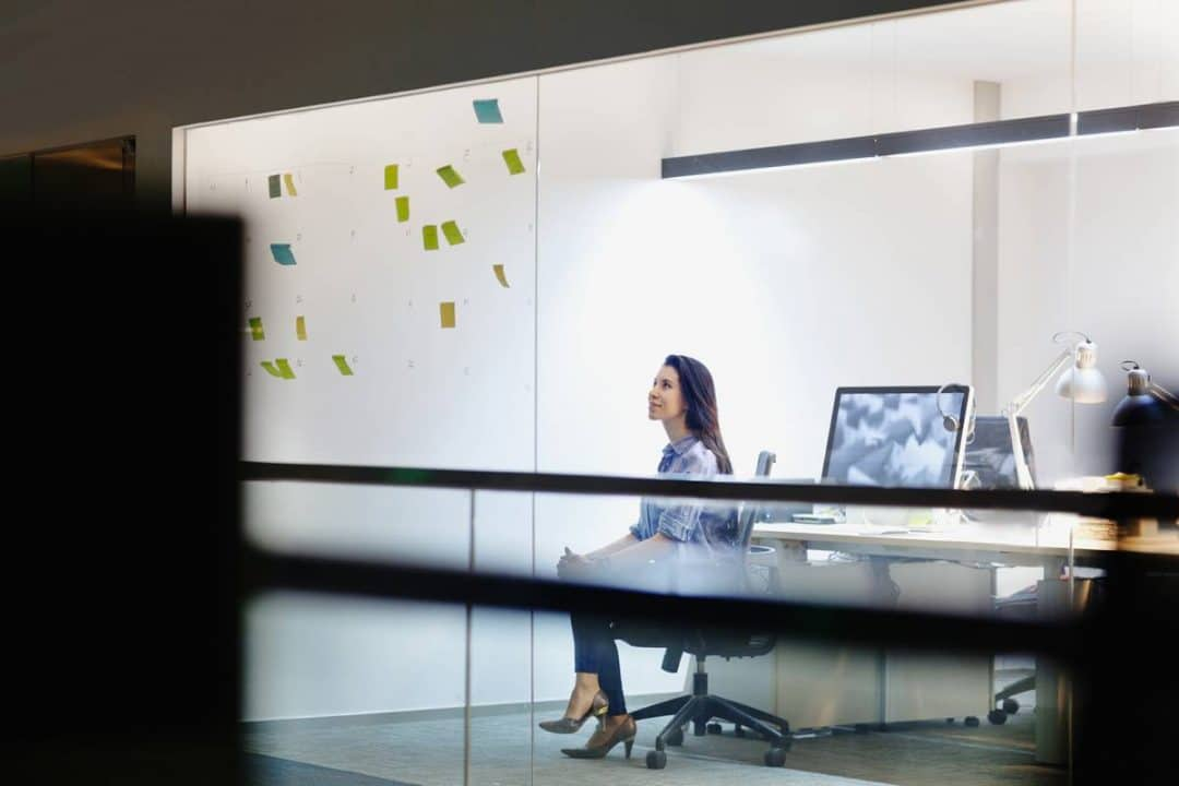 Female entrepreneur looking at a business plan with a computer behind her