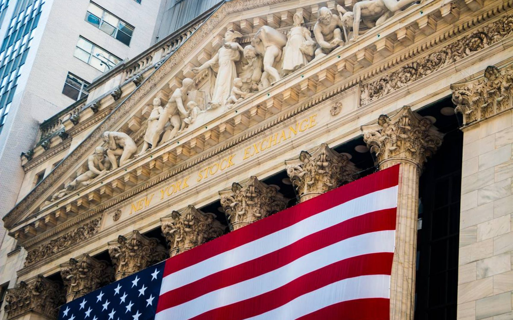 New York Stock Exchange Building on Wall Street with American Flag draped across the front