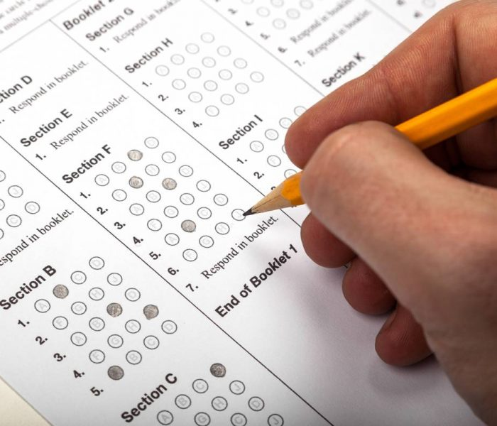 Close up of a hand holding a pencil while filling in bubbles on a standardized test answer sheet