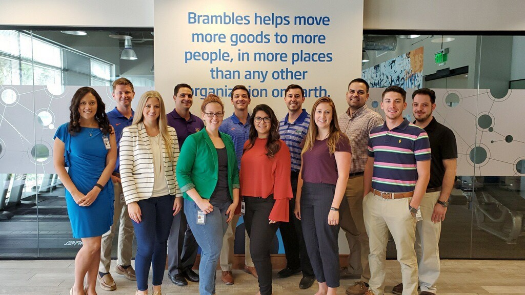12 people stand in front of a Brambles logo
