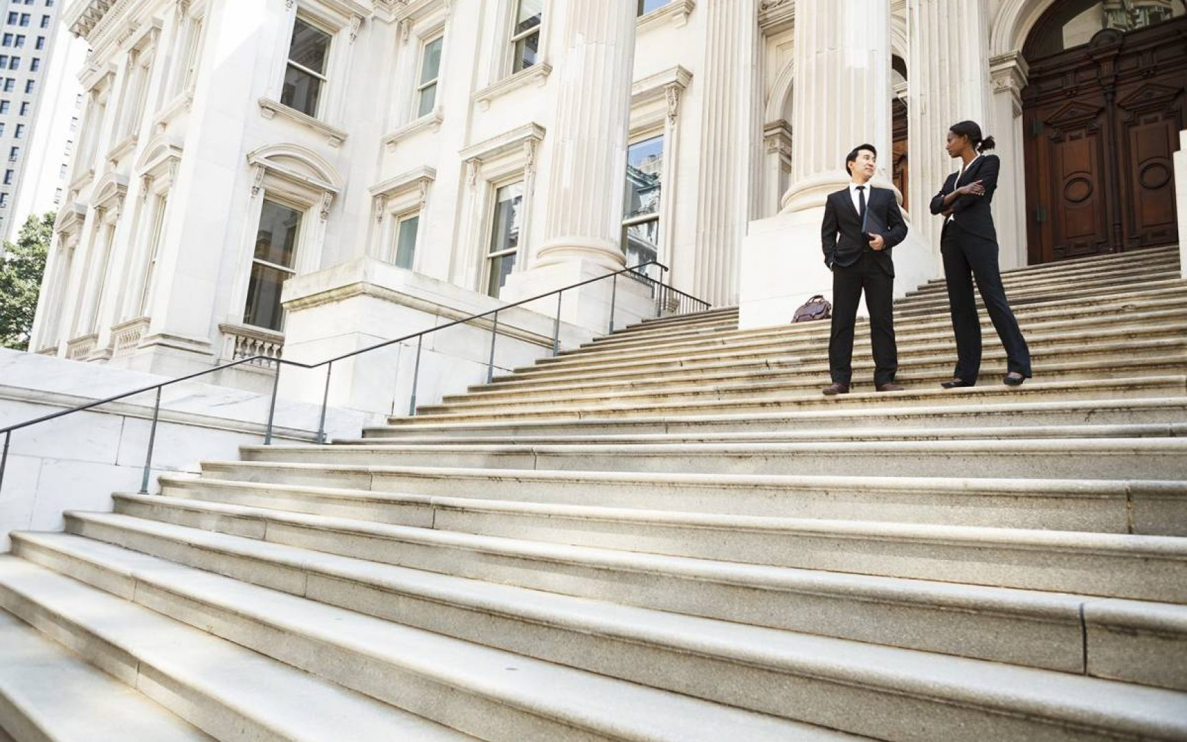 Male and female lawyer talking on courthouse steps