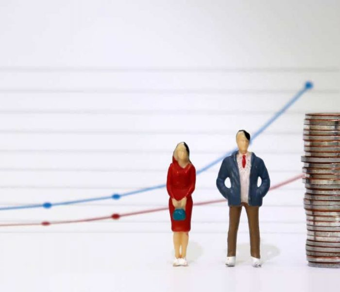 A miniature couple standing next to a pile of coins with a linear graph. The concept of the wage gap between men and women, which grows larger over time.