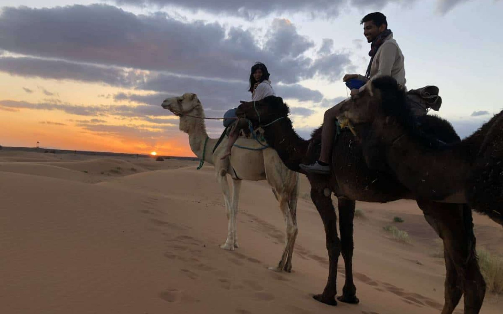 Two students riding camels on sandy dunes at sunset