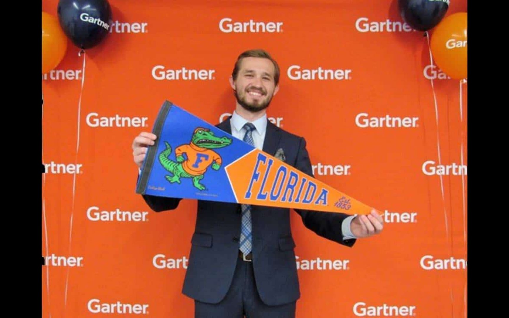David Ousley holds a University of Florida pennant in front of a Gartner step and repeat