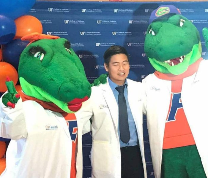 Justin Kim with Albert and Alberta mascots in lab coats