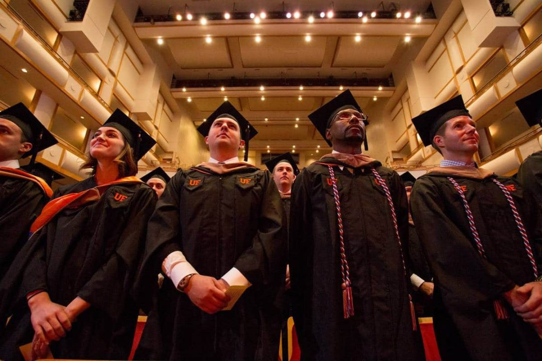 Upward angle of UF MBA students in graduation robes and caps