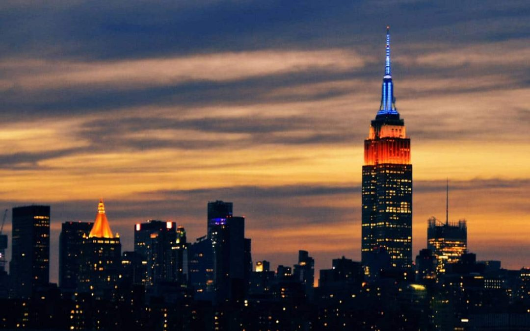 New York City skyline with Empire State Building lit up with orange and blue lights