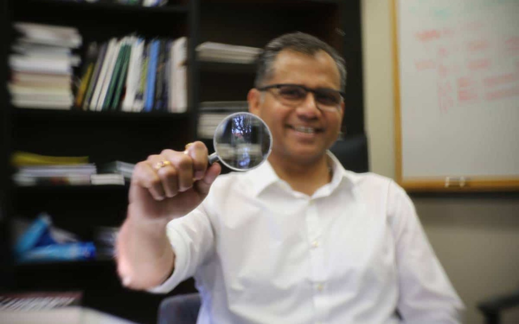 Warrington faculty member Anuj Kumar sitting in his office by a bookshelf holding up a magnifying class that reflects the courtyard outside of his office.