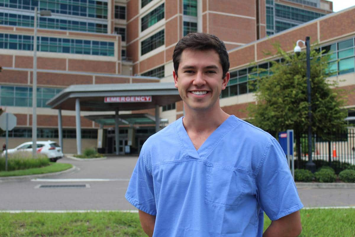 Brandon Climenhage stands in front of UF Health Shands Hospital